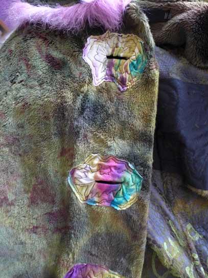 Koos van Akker buttonholes on green faux fur wearable art coat, long shearling coat with pink fake fur tails